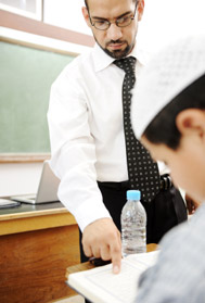 Muslim Arabic male teacher in class teaching Koran