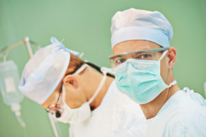 Portrait of surgeon medic in front of surgeons perfoming operati
